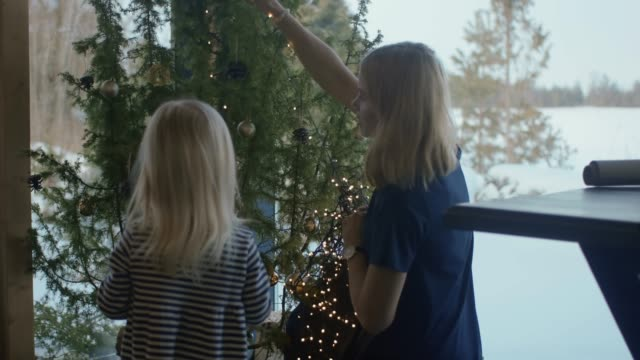 mother and daughter decorating christmas tree (slow motion) - cottage stock videos & royalty-free footage