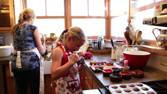 ms pan mother and daughter decorating cupcakes / lamy, new mexico, united states - renovierung themengebiet stock-videos und b-roll-filmmaterial