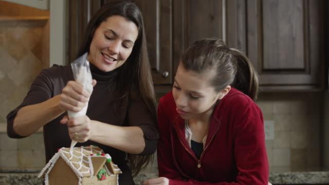 vídeos de stock, filmes e b-roll de ms mother and daughter (8-9) decorating gingerbread house in kitchen / orem, utah, usa - orem utah