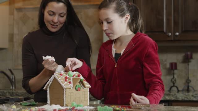 vidéos et rushes de ms tu mother and daughter (8-9) decorating gingerbread house in kitchen / orem, utah, usa - orem