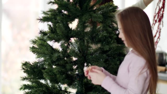 mother and daughter decorating the christmas tree - decorating the christmas tree stock videos & royalty-free footage