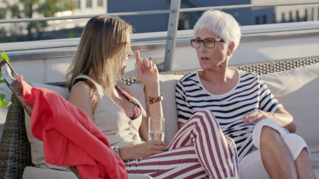 mother and daughter discussing together the world on rooftop terrace. - angesicht zu angesicht stock-videos und b-roll-filmmaterial