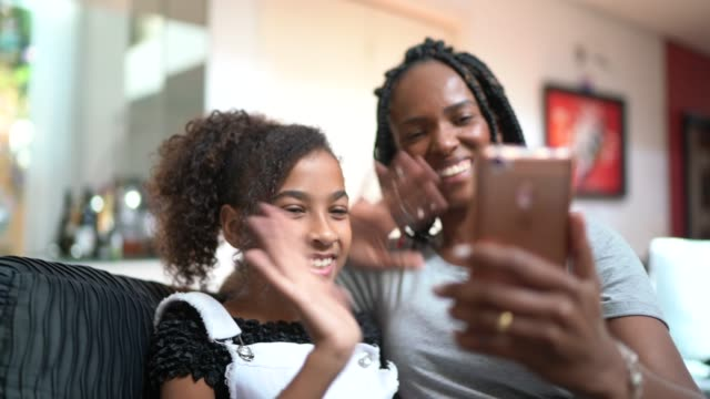 mother and daughter doing a video call at home - pre adolescent child stock videos & royalty-free footage