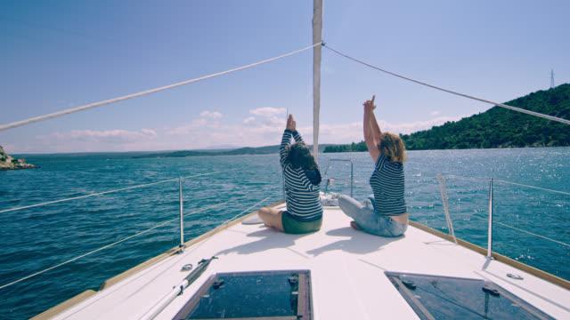 vidéos et rushes de ws mère et la fille faisant des exercices de respiration sur un voilier - famille avec un enfant