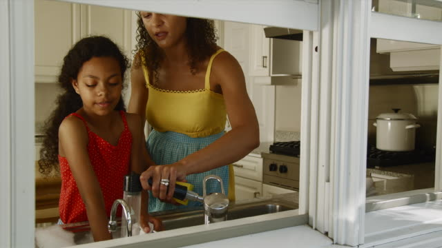 ms mother and daughter (12-13) doing dishes in kitchen / edmonds, washington state, usa - diska bildbanksvideor och videomaterial från bakom kulisserna