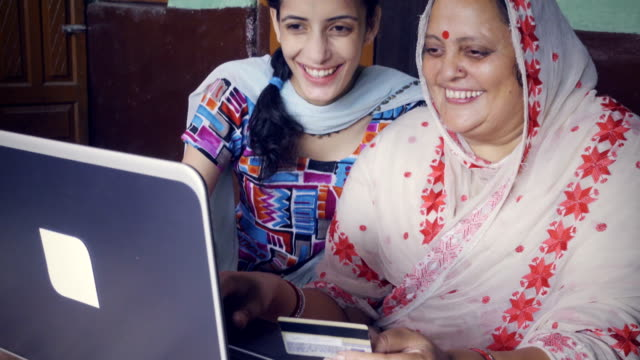 mother and daughter doing online shopping at home. - indian ethnicity stock videos & royalty-free footage