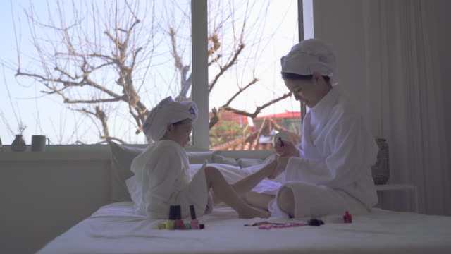 mother and daughter doing pedicure in the bedroom - painting toenails stock videos & royalty-free footage
