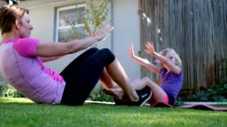 Mother and daughter doing some sit-ups outside in their yard