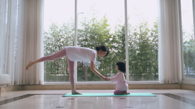 mother and daughter doing yoga at home - 弓のポーズ点の映像素材/bロール
