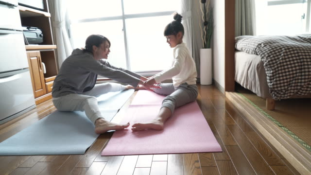 mother and daughter doing yoga in the room - フローリング点の映像素材/bロール