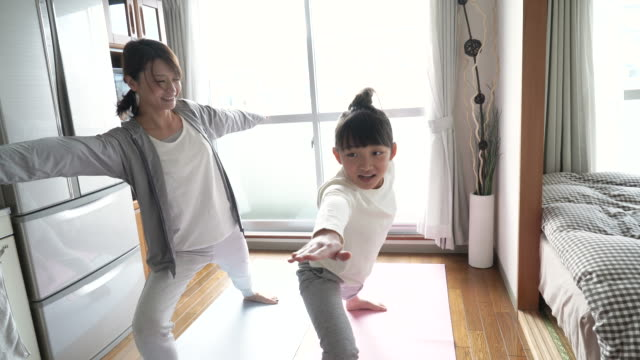vídeos y material grabado en eventos de stock de mother and daughter doing yoga in the room - exclusivamente japonés
