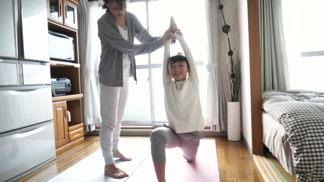 Mother and daughter doing yoga in the room