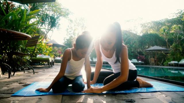 Mutter und Tochter beim Yoga in der Nähe von Schwimmbad