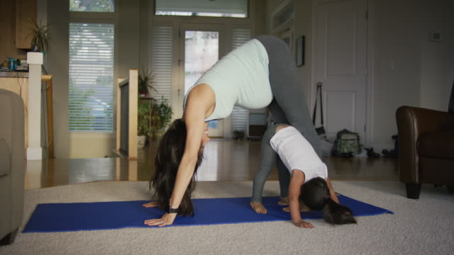 mother and daughter doing yoga - domestic life stock videos & royalty-free footage