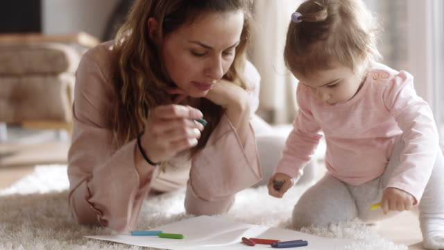 mother and daughter drawing on the floor at living room - crayon stock videos and b-roll footage
