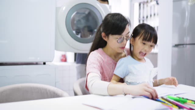 mother and daughter drawing together, father doing laundry behind them - housework stock videos & royalty-free footage