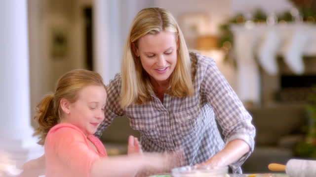 vidéos et rushes de mother and daughter drop and pound cookie dough balls on kitchen counter-top (dolly-shot) - baking