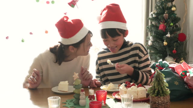 Mother and daughter eating cake at Christmas party