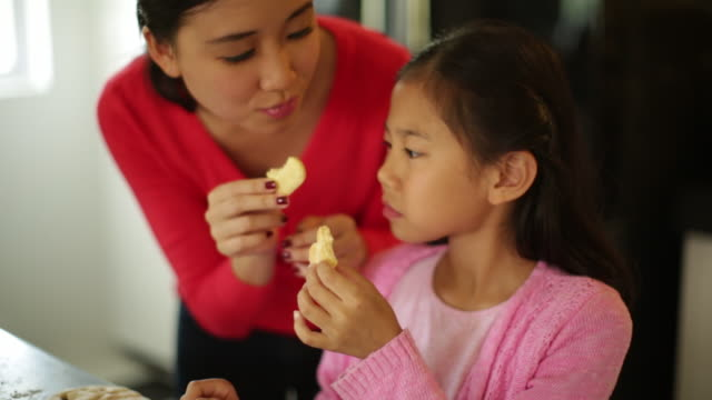 cu mother and daughter eating freshly made cookies - snack stock videos & royalty-free footage