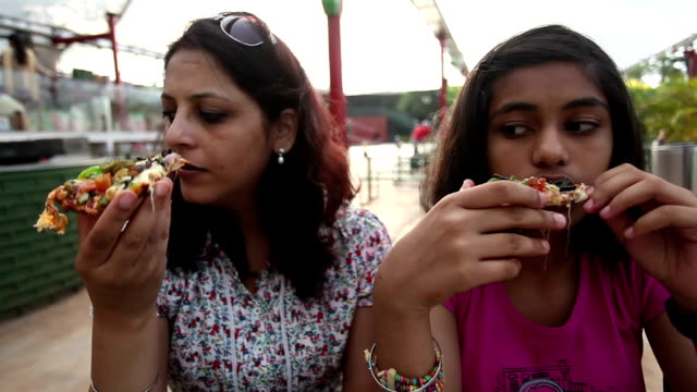 mother and daughter eating pizza - indian mom stock videos & royalty-free footage