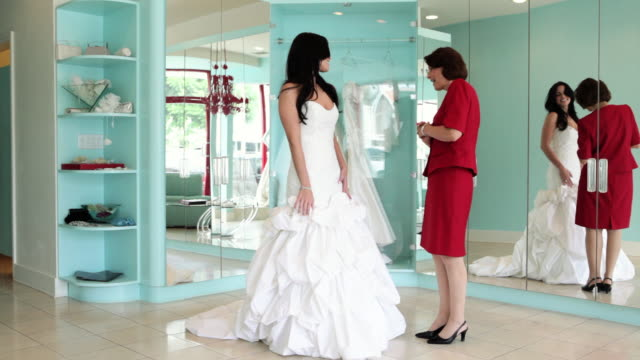 Mother and daughter embracing, daughter trying on wedding dress