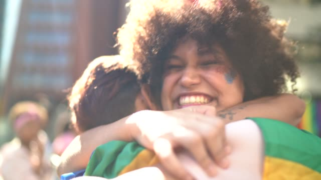 vídeos de stock e filmes b-roll de mother and daughter embracing during lgbtqi parade - brazilian ethnicity