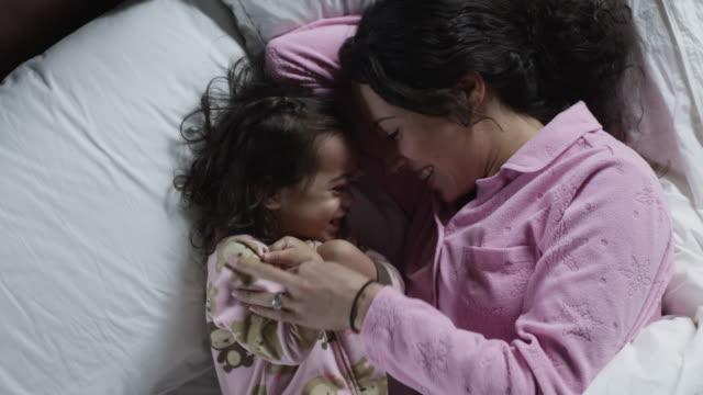 ms mother and daughter (2-3) embracing in bed / orem, utah, usa - orem bildbanksvideor och videomaterial från bakom kulisserna