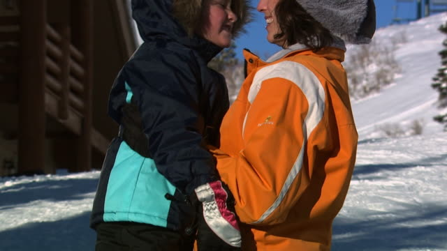 a mother and daughter embracing on a ski hill - see other clips from this shoot 1169 stock videos & royalty-free footage