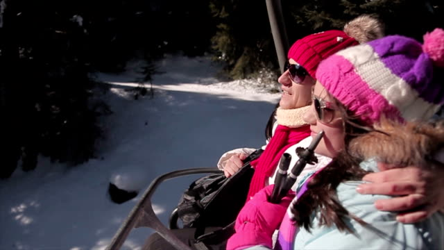 vídeos de stock e filmes b-roll de mother and daughter enjoying on ski lift on winter vacation - casaco de esqui