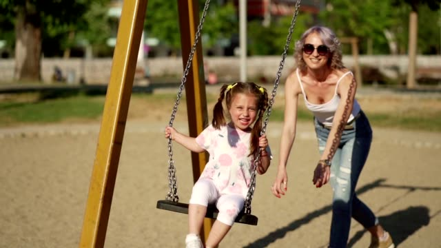 mother and daughter enjoying summer day at a playground - swinging stock videos & royalty-free footage