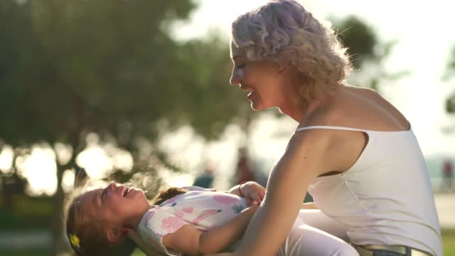 mother and daughter enjoying summer day in the park - tickling stock videos & royalty-free footage