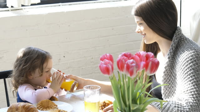 mother and daughter enjoying their breakfast at home - orange juice stock videos & royalty-free footage