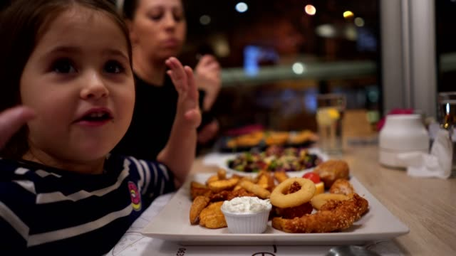 mother and daughter enjoying their food - pollo video stock e b–roll