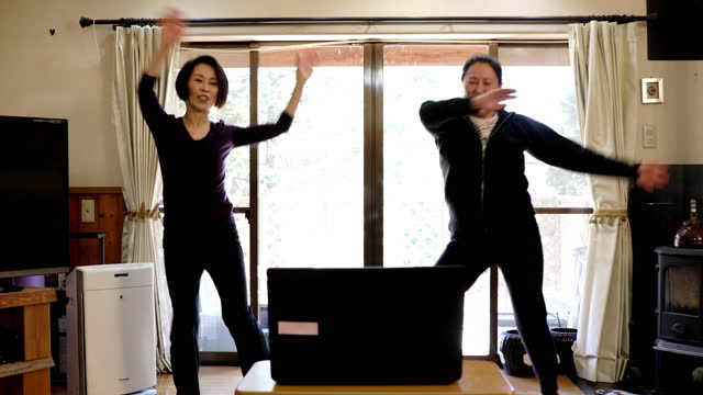 mother and daughter exercising at home online via laptop - 40 44 years stock videos & royalty-free footage