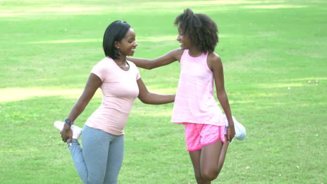 mutter und tochter trainieren im park, dehnung - auf einem bein stock-videos und b-roll-filmmaterial