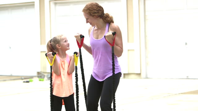 Mother and daughter exercising, using resistance bands