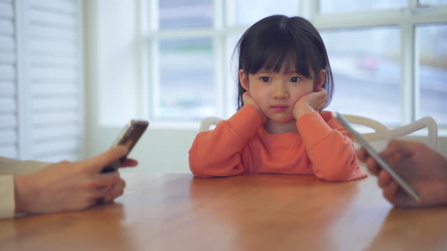 mother and daughter, family using smartphones and child feeling bored at a table - kindertag stock-videos und b-roll-filmmaterial