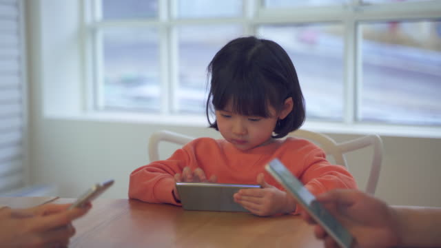 mother and daughter, family using smartphones at a table - kindertag stock-videos und b-roll-filmmaterial