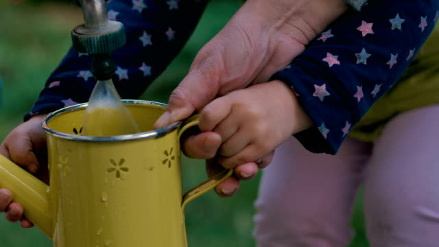 mother and daughter filling watering can for watering plants in the garden - planting stock videos & royalty-free footage