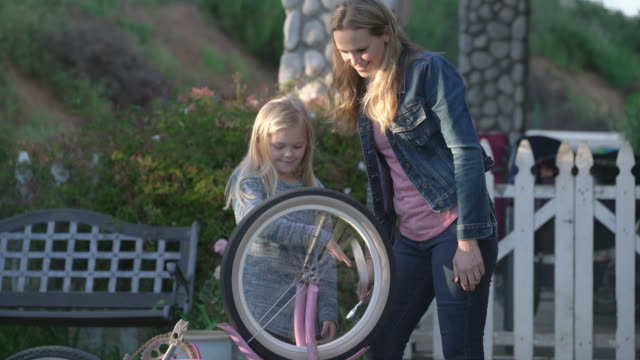 vídeos de stock, filmes e b-roll de ms mother and daughter fixing a bicycle together - jaqueta jeans