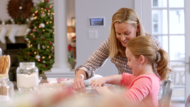 mother and daughter flatten cookie dough with rolling-pins, daughter chooses candy-cane cookie-cutter to shape with (dolly-shot) - moulding trim stock videos & royalty-free footage