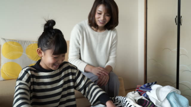 mother and daughter folding the laundry looking happily in the room - たたむ点の映像素材/bロール
