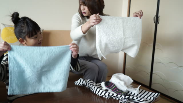 mother and daughter folding the laundry looking happily in the room - lavori di casa video stock e b–roll