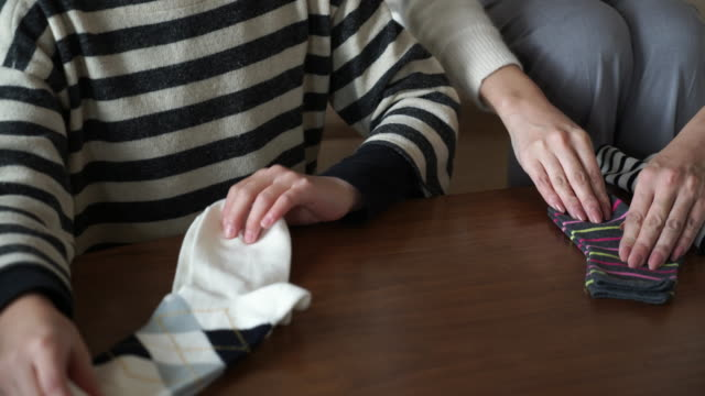 mother and daughter folding the laundry looking happily in the room - solo giapponesi video stock e b–roll