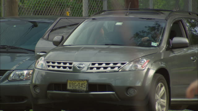 vidéos et rushes de ms mother and daughter getting into suv with man driving and leaving playground parking lot/ fanwood, new jersey - parking
