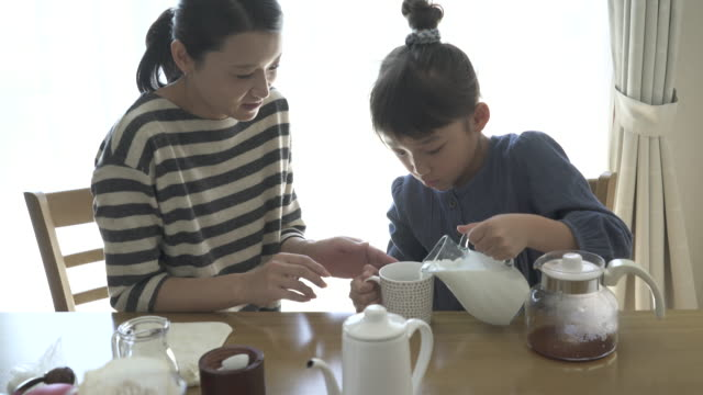 mother and daughter have a coffee break in the room - コーヒーカップ点の映像素材/bロール