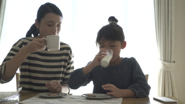mother and daughter have a coffee break in the room - solo giapponesi video stock e b–roll