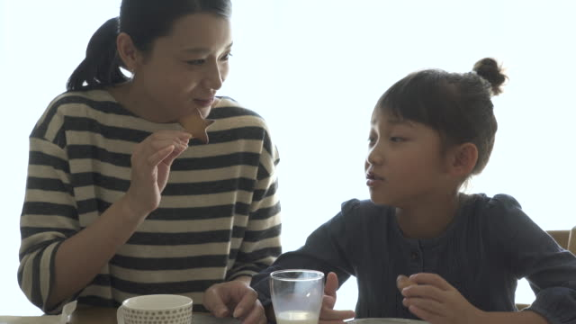 mother and daughter have a coffee break in the room - スイーツ点の映像素材/bロール