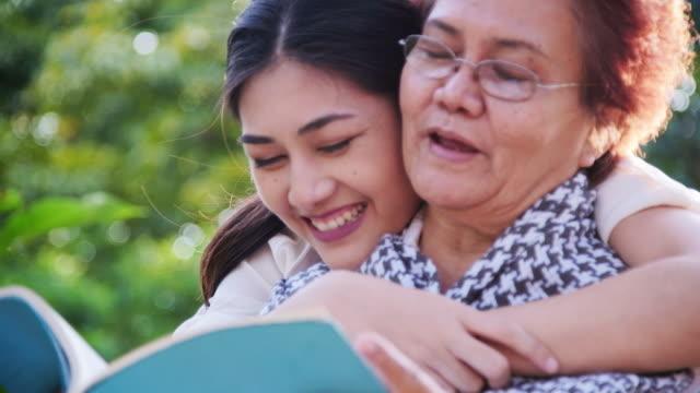 vídeos de stock, filmes e b-roll de mãe e filha têm um momento feliz juntos no parque. mãe de surpresas da filha com um abraço por trás - acontecimentos da vida