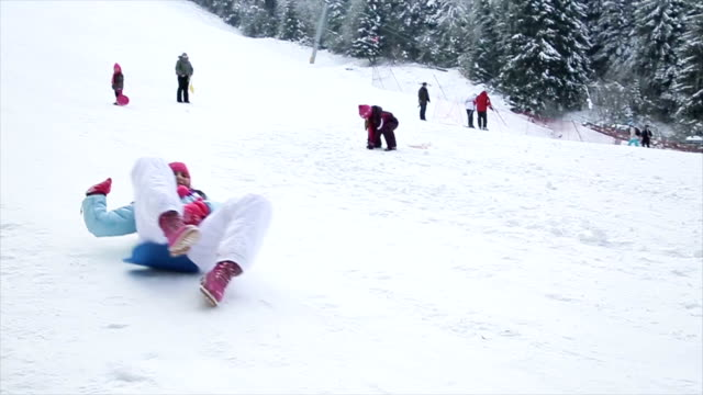 Mother and daughter have fun with toboggan in winter ski center